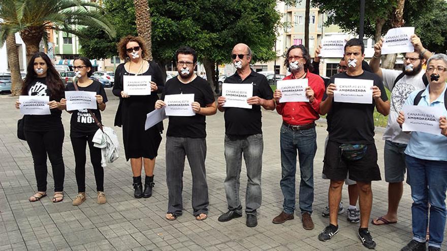 Miembros del movimiento canario contra las prospecciones petrolíferas que se tapan la boca con cinta adhesiva a modo de protesta.
