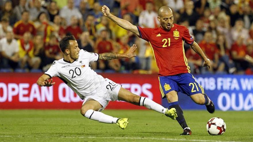 El centrocampista de la selección española de fútbol David Silva chuta ante Ergys Kace, de Albania, en el estadio José Rico Pérez, en Alicante. EFE/Joaquín Reina