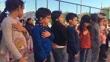 Celebración del Día de la Constitución en un colegio público de Murcia: niños con la mano en el pecho a ritmo de himno