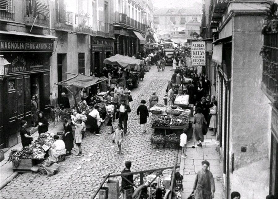 Peatones, vehículos y comercio ocupando la calle. Ene ste caso es en el mercado que se montaba en la Corredera Baja de San Pablo, pero en mayor o menor medida hubo un momento en que fue lo habitual.