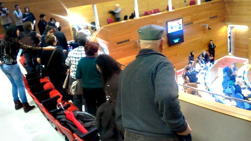 Personas afectadas por las preferentes de las cajas gallegas protestan en un pleno del Parlamento en diciembre de 2012