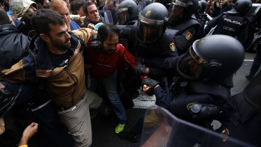 Pro-referendum supporters clash with Spanish National Police outside the Ramon Llull school assigned to be a polling station by the Catalan government in Barcelona, Spain, early Sunday, 1 Oct. 2017. Catalan pro-referendum supporters vowed to ignore a police ultimatum to leave the schools they are occupying to use in a vote seeking independence from Spain.