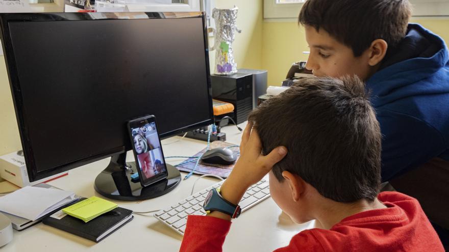 Dos estudiantes hablando con sus compañeros por videollamada durante el confinamiento.