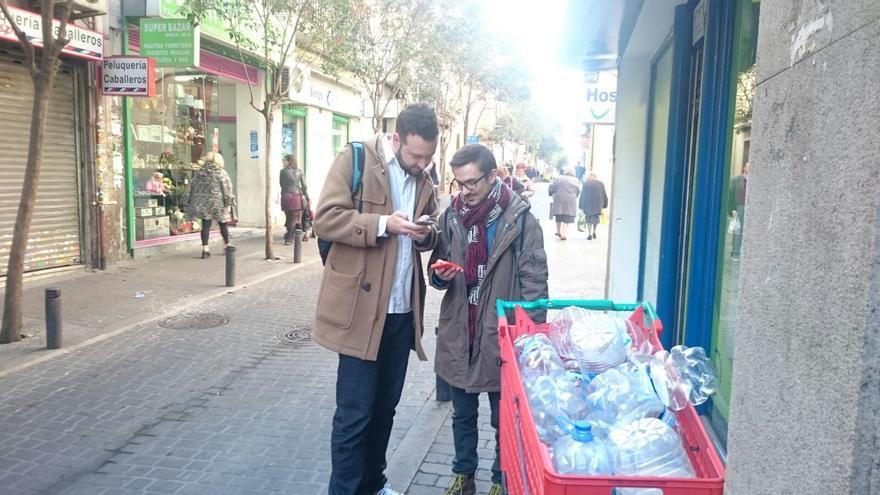 Juanlu Sánchez y Antonio Rull enviando alertas junto a un colegio electoral. Las garrafas vacías son ajenas a eldiario.es