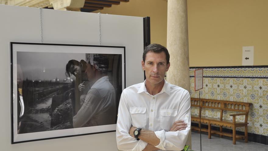 El fotógrafo Miguel Sebastián, junto a una de las imágenes de la exposición.