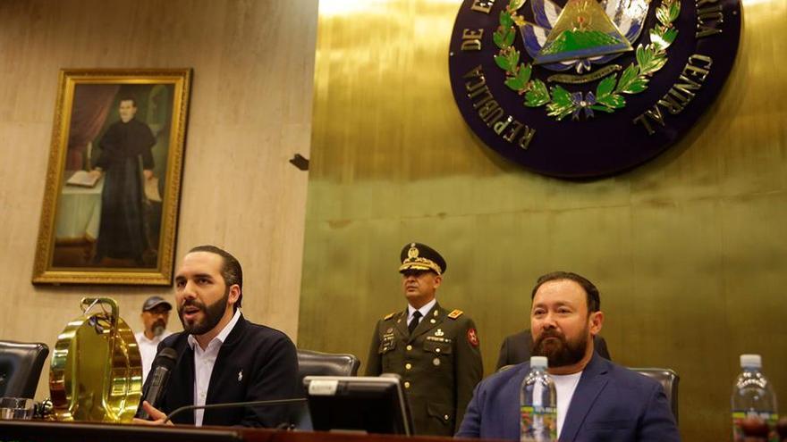 El presidente de El Salvador, Nayib Bukele (i), habla junto al diputado Guillermo Gallegos (d), del partido Gran Alianza por la Unidad Nacional, durante una sesión en el Congreso este domingo, en San Salvador.