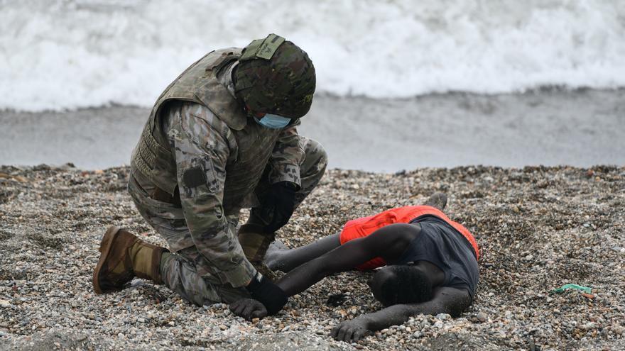 Un militar español atiende a un migrante exhausto tras llegar nadando a Ceuta.