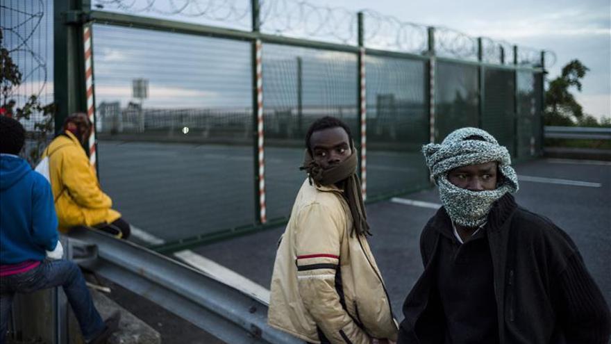 Un grupo de inmigrantes espera para saltar una valla e intentar tomar un tren en su ruta hacia Inglaterra, en Calais (Francia). / Efe.