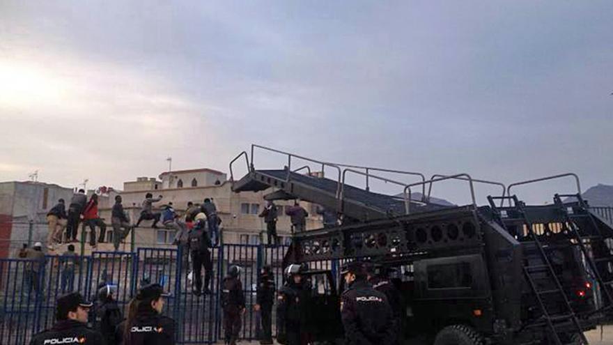 La Policía Nacional intenta bajar a los inmigrantes encaramados en la valla. Todos fueron devueltos a Marruecos./ Blasco de Avellaneda