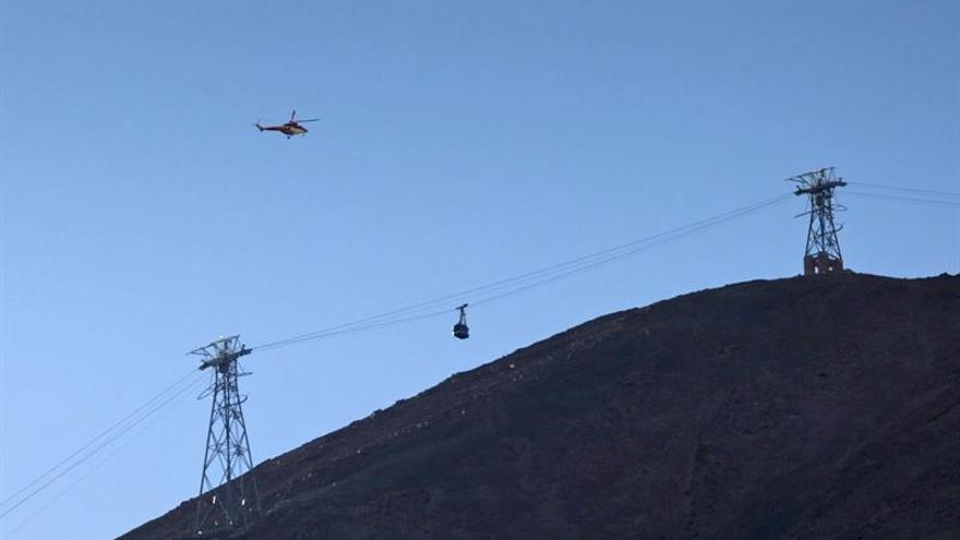 Uno de los helicópteros de rescate sobrevuela la instalación del teleférico en el Teide