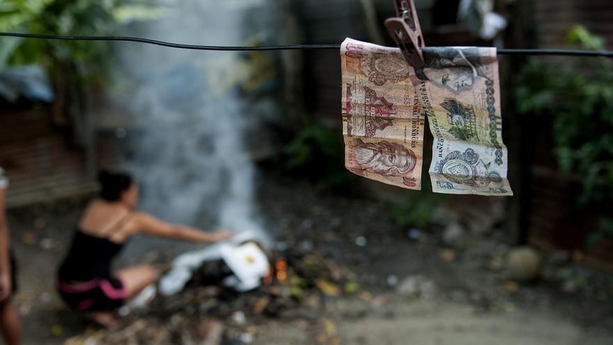 15 lempiras (US$0.50) secándose en el tendedero mientras Artemis quema unos envases de comida china después de comer. Los billetes están mojados después de que los adolescentes jugaran a una batalla campal de cubos de agua.