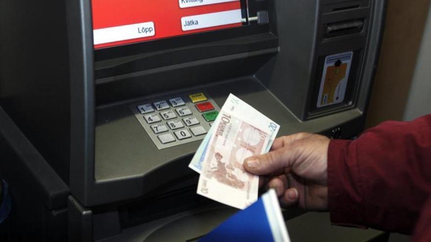 Un cliente saca dinero de un cajero automático.