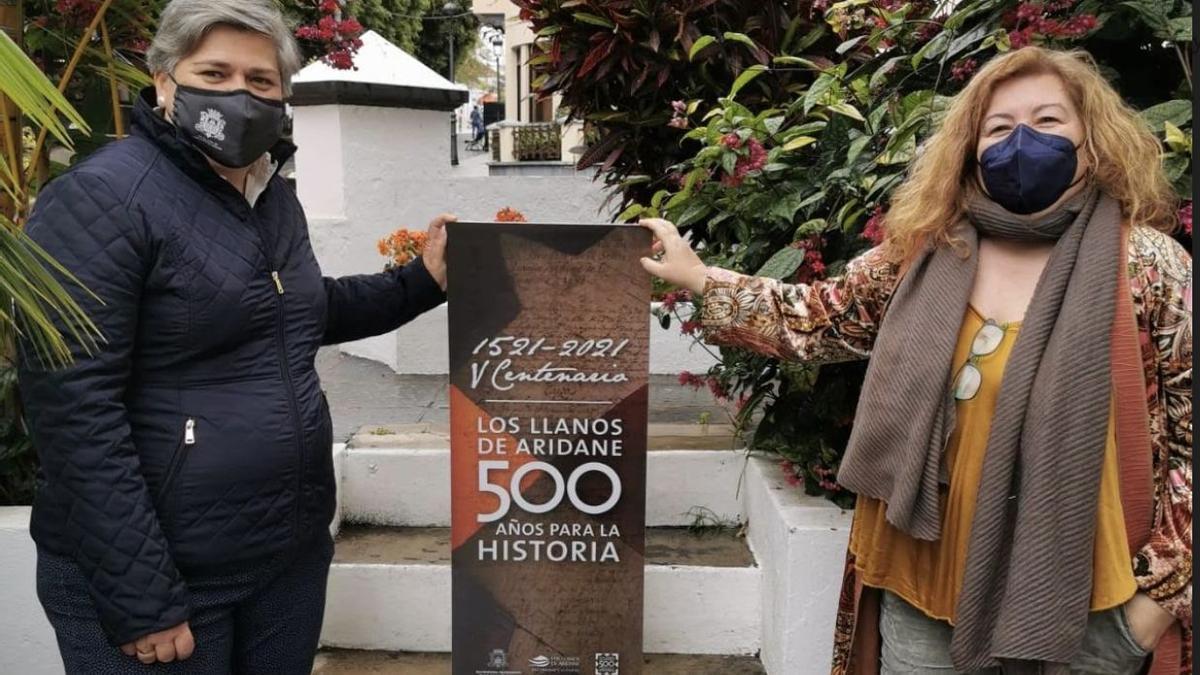 Noelia García Leal, alcaldesa del Ayuntamiento de Los Llanos de Aridane,  y Charo González, concejal de Cultura, con el  cartel del 'V Centenario de la Fundación del Lugar de Los Llanos'