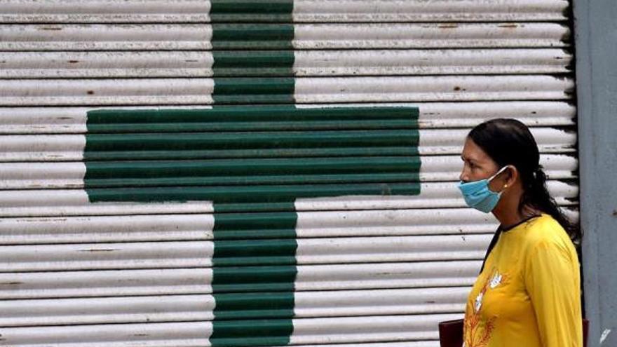 Una mujer india pasa por una farmacia cerrada durante el cierre para frenar la propagación del COVID-19 en Guwahati, Assam, India, el 11 de julio de 2020.