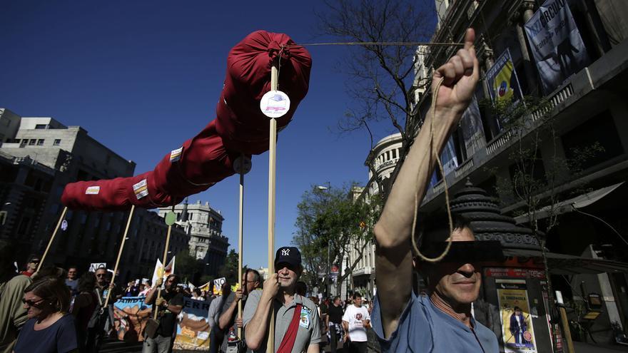 Un grupo de manifestantes cargan con una simulación de un chorizo, símbolo de uno de los lemas del 15M. / Olmo Calvo.