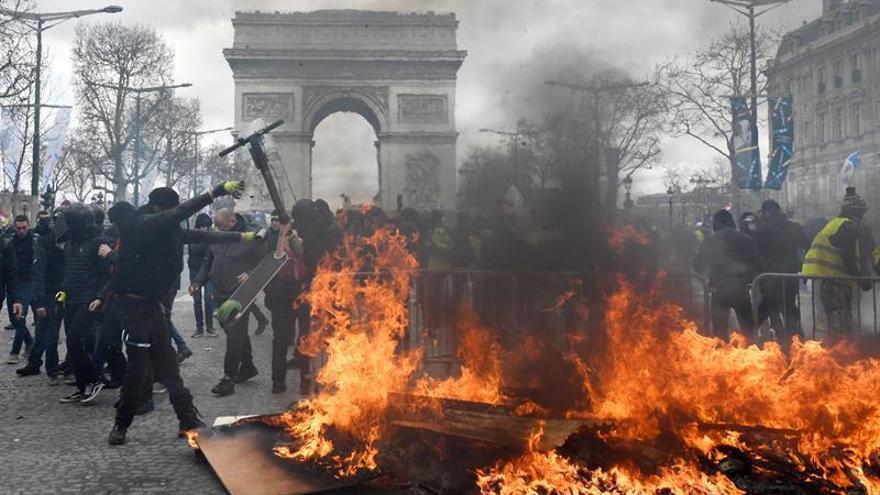 Los chalecos amarillos se enfrentan a las fuerzas policiales en los Campos Elíseos en París, Francia