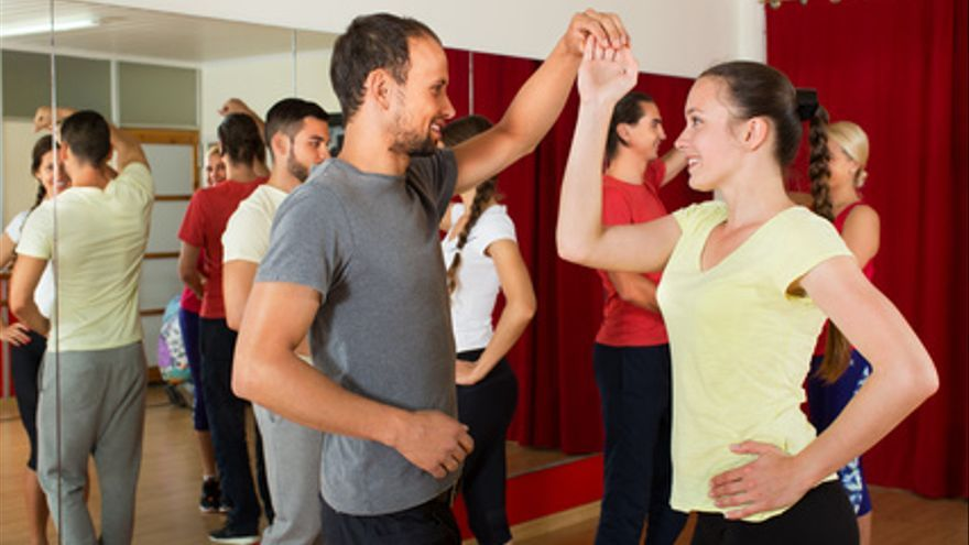 Smiling adults dancing bachata together in the dance studio
