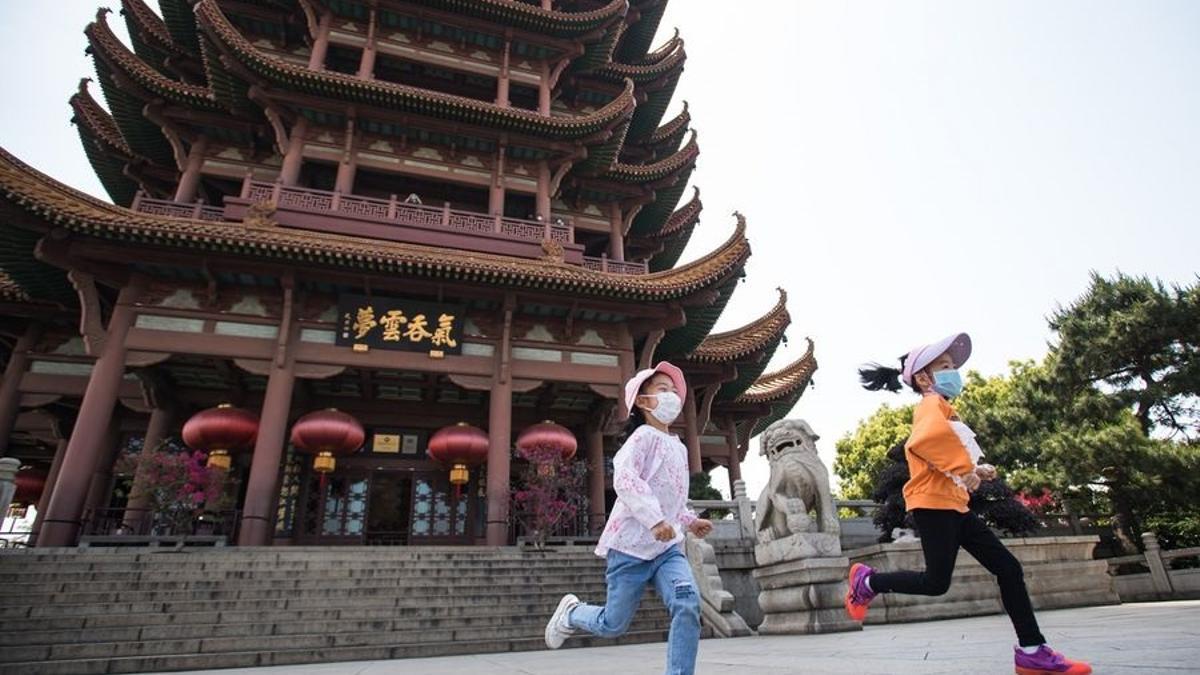 Niñas con mascarilla jugando en Wuhan, China