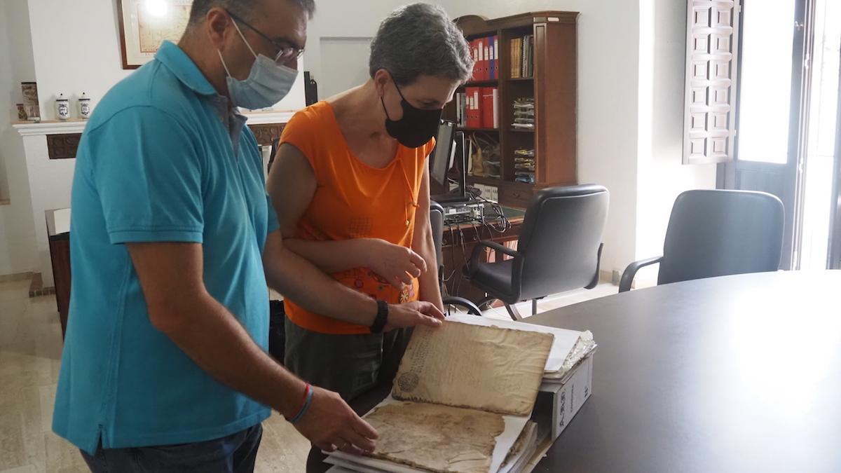 La directora del Archivo ojea un documento en mal estado.