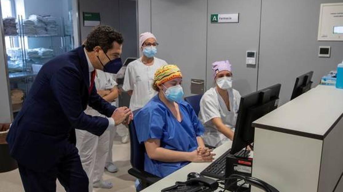 El presidente de la Junta, Juan Manuel Moreno, junto a personal sanitario de un Hospital de Emergencia COVID-19.