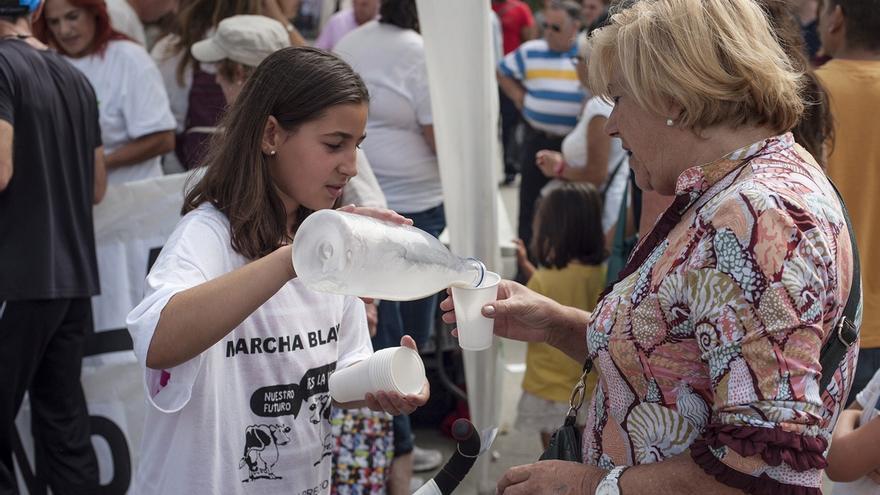 Un niña sirve leche gratis a los vecinos como modo de protesta ante la industria láctea. | JAVO DÍAZ
