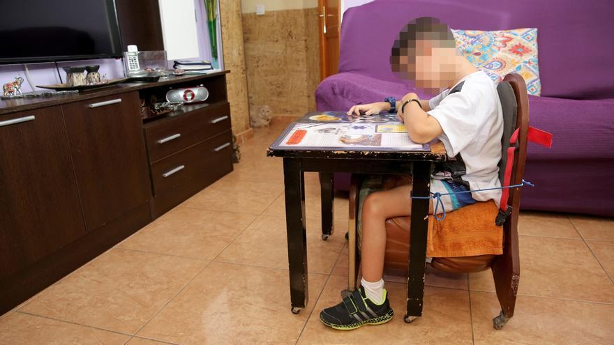 Yadey sentado correctamente en un pupitre en su casa