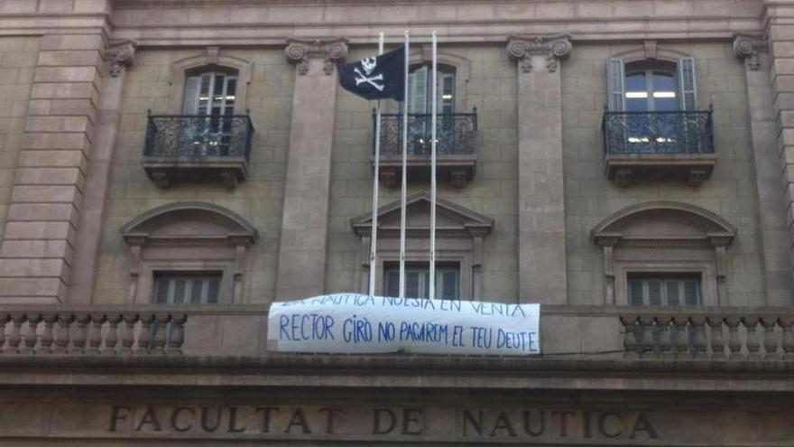 """La façana de l'edifici de la FNB, amb la bandera pirata i una pancarta on es llegeix """"Rector Giró, no pagarem el seu deute""""."""