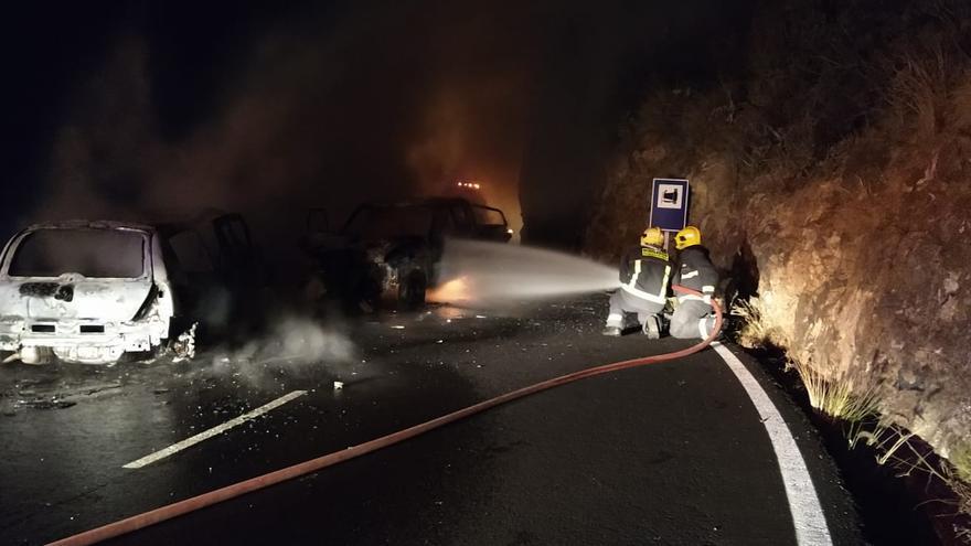 Dos bomberos en la tareas de extinción del incendio de dos vehículos tras una colisión frontal en la carretera de El Time.