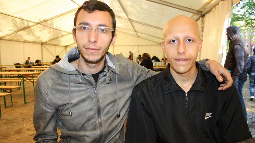 Los hermanos Mohammed y Khaleel Turani en la carpa donde se reparte comida frente a las oficinas del edificio de asuntos sociales de Berlín donde van a inscribirse los refugiados.
