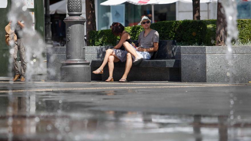 Dos personas se refugian a la sombra de las altas temperaturas   ÁLVARO CARMONA