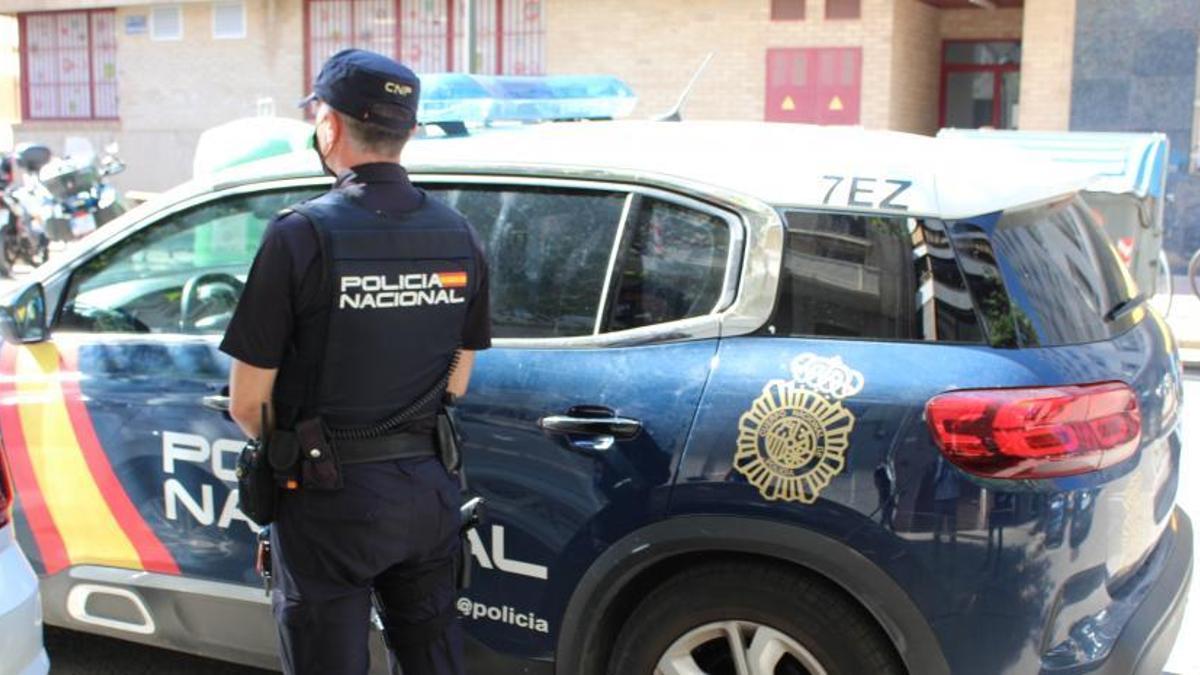 Un agente de Policía Nacional junto a un vehículo patrulla en una imagen de archivo.