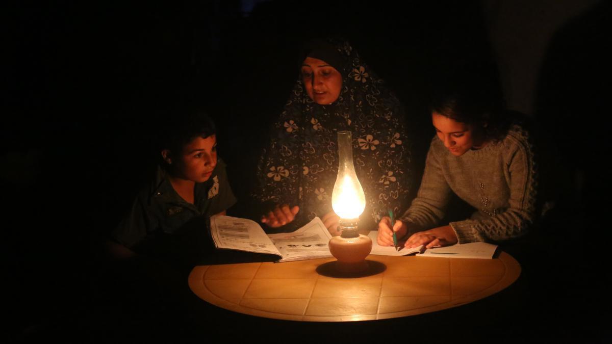 Una madre ayuda a sus hijos a estudiar, iluminados por la luz de un candil debido a la falta de electricidad en Gaza.