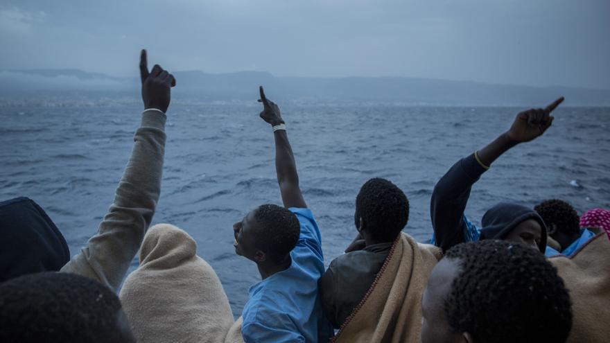 Refugiados y migrantes africanos celebran su llegada a Italia a bordo del Golfo Azurro, la ONG española Proactiva Open Arms, tras ser rescatados de la costa libia.
