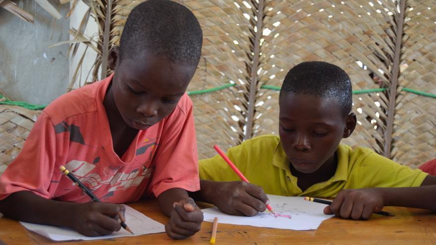 Dos niños acogidos por la ONG Aytimoun Yo pintando.