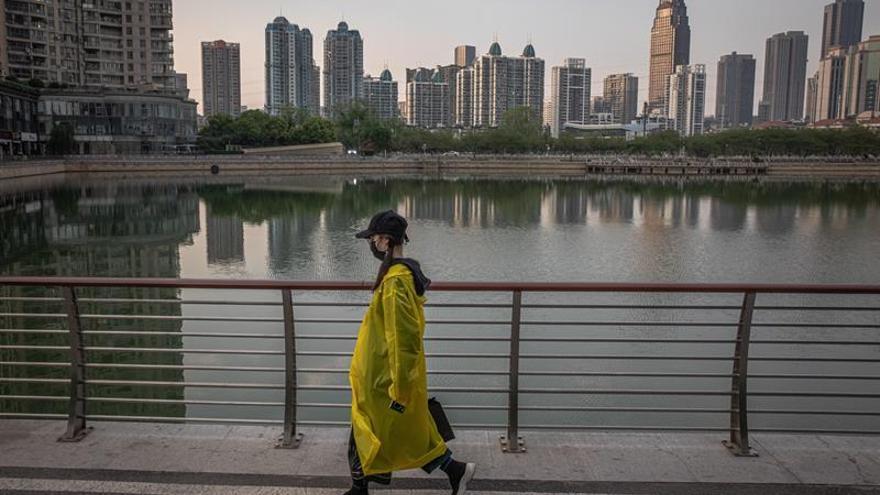Una mujer camina junto a un lago de Wuhan (China) tras el fin del confinamiento