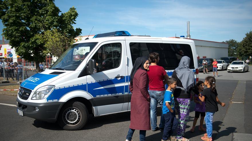 Refugiados parados al lado de un vehículo de la policía antes de una visita de la canciller alemana Angela Merkel al alojamiento de refugiados en Heidenau, Alemania, 26 de agosto de 2015/ Foto: Arno Burgi - AP