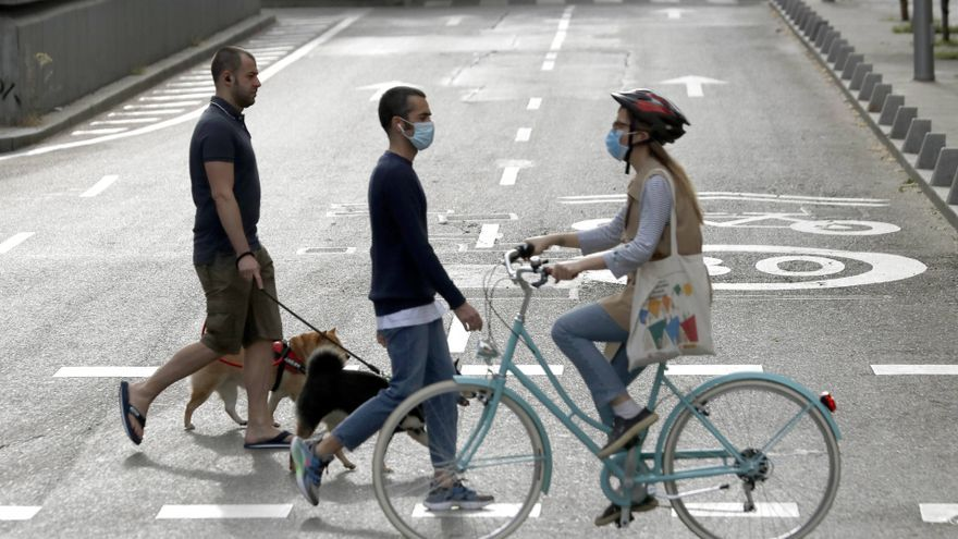 Personas con o sin mascarilla en una calle de Madrid.