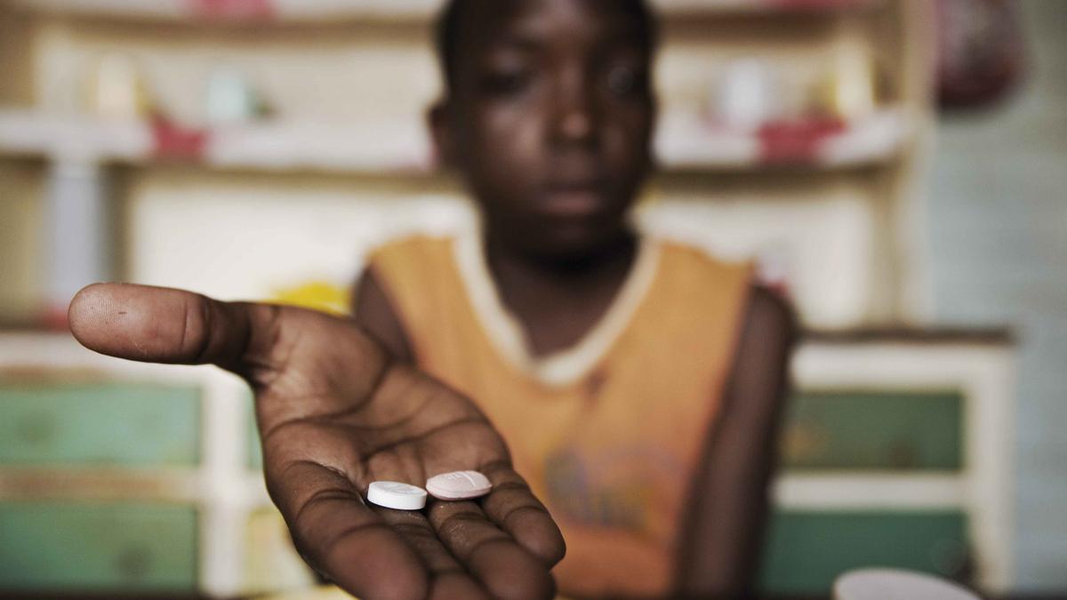 Un niño posa con su tratamiento contra el VIH en una clínica de Zimbabue