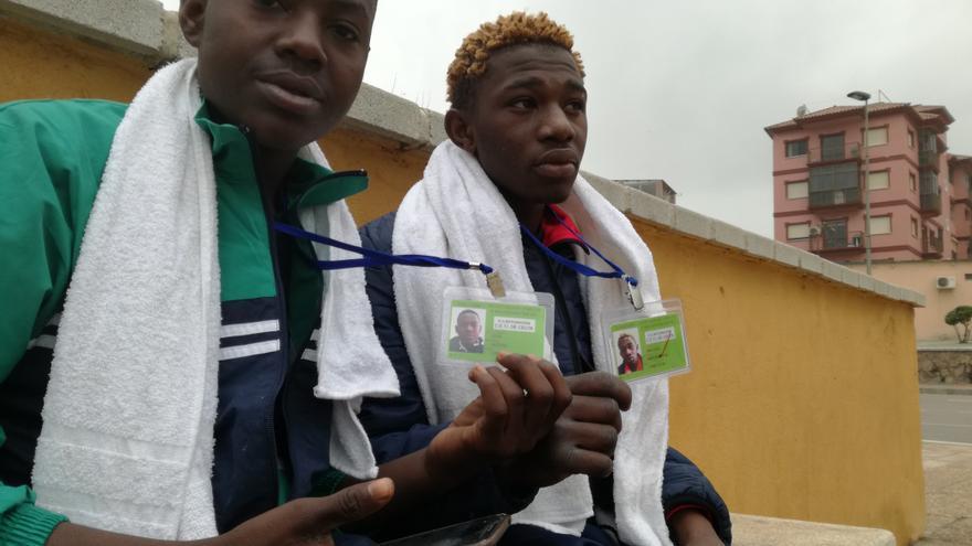 Issa Bobbo y Amadou Moustapha, recién llegados a Ceuta, muestran sus tarjetas del Centro de Estancia Temporal.