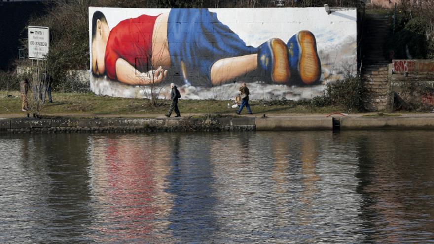 Un grafitti que emula la fotografía de Aylan en la playa frente al río Main en Frankfurt. / Michael Probst - AP Photo