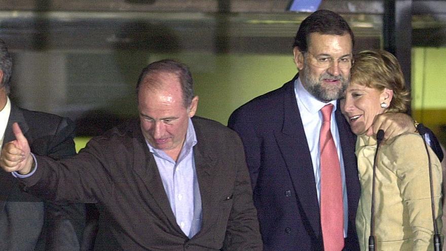 ELECCIONES AUTONOMICAS. VICTORIA DEL PP:MADRID. 26-10-2003.- La candidata del Partido Popular a la presidencia de la Comunidad de Madrid, Esperanza Aguirre, es abrazada por el secretario general del PP, Mariano Rajoy, mientras el vicepresidente primero del Gobierno y ministro de Economía, Rodrigo Rato, saluda a los seguidores del partido que se reunieron esta noche en la calle Génova para celebrar el triunfo de Aguirre en las elecciones autonómicas celebradas hoy en la región. EFE/GUSTAVO CUEVAS