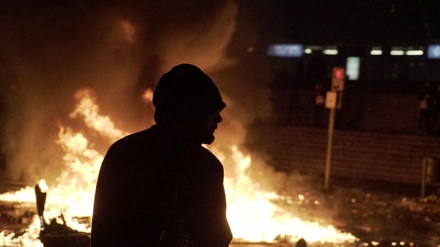 Un manifestante encapuchado ante una hoguera en las inmediaciones del Camp Nou Foto: Sònia Calvó