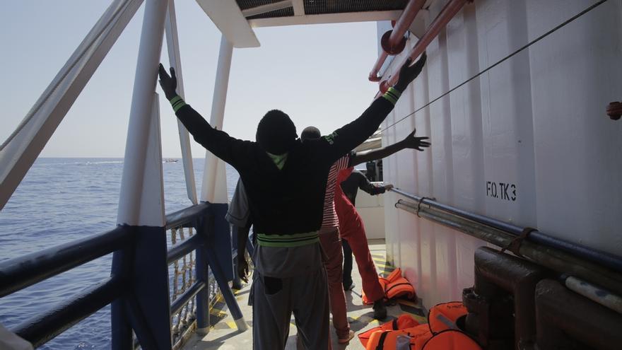 Un hombre celebra su llegada a bordo del Dignity I, uno de los buques de salvamento de MSF. El alivio que sienten al ser rescatados es e inmenso. La emoción es enorme y muchos la expresan de rodillas y con los brazos levantados para dar gracias y rezar por haber llegado sanos y salvos. Para algunos este momento supone el fin de una odisea de meses o incluso años. Fotografía: Agus Morales/MSF