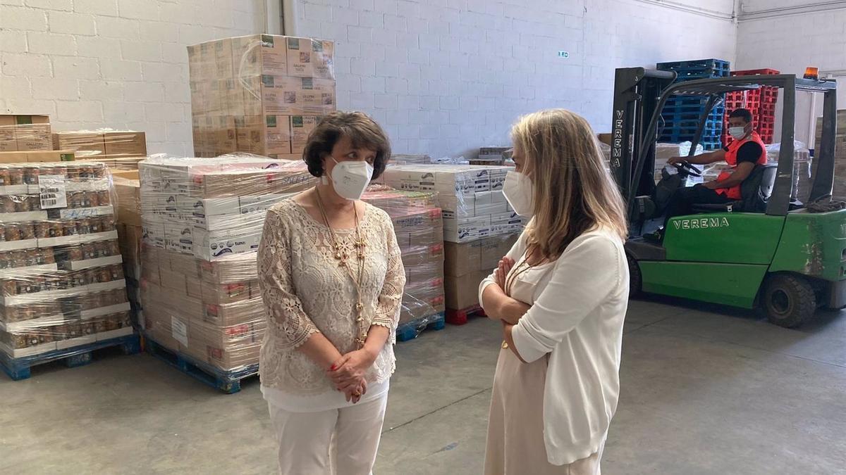 La subdelegada del Gobierno central en Córdoba, Rafaela Valenzuela (izda.), visita el almacén de alimentos de Cruz Roja.
