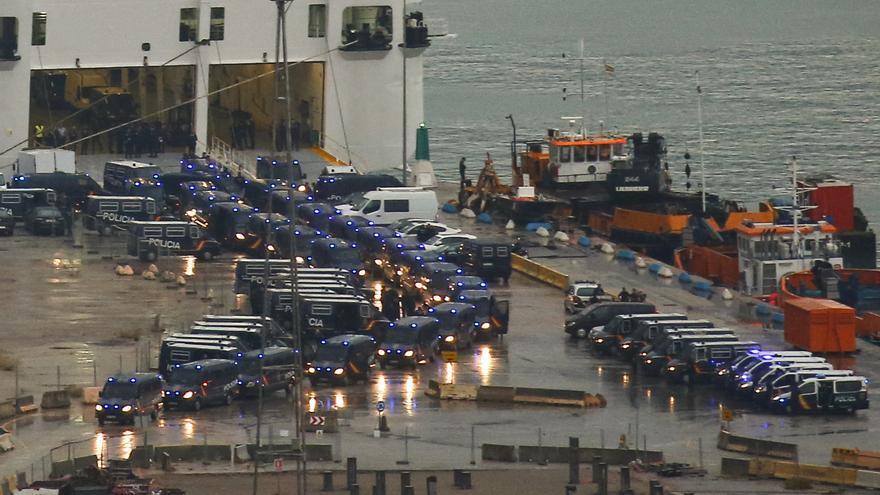 Vehículos policiales abandonan el puerto donde están alojados los agentes a primera hora del domingo.