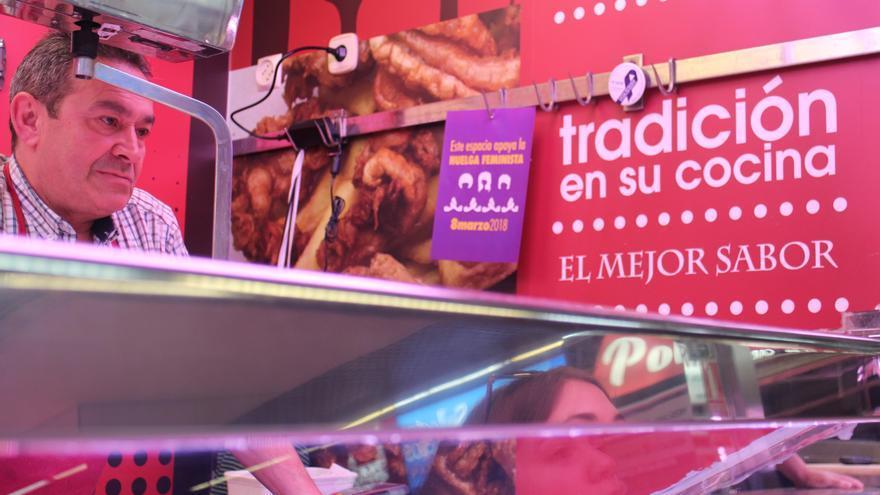 El encargado de un puesto del mercado de Santa María de la Cabeza cuelga el cartel de la huelga feminista