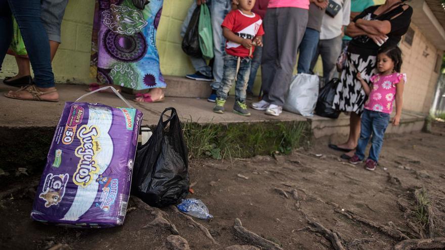 Familiares de reclusas llevan víveres para los niños que viven en PNFAS mientras hacen fila para ingresar a la sala de visitas.