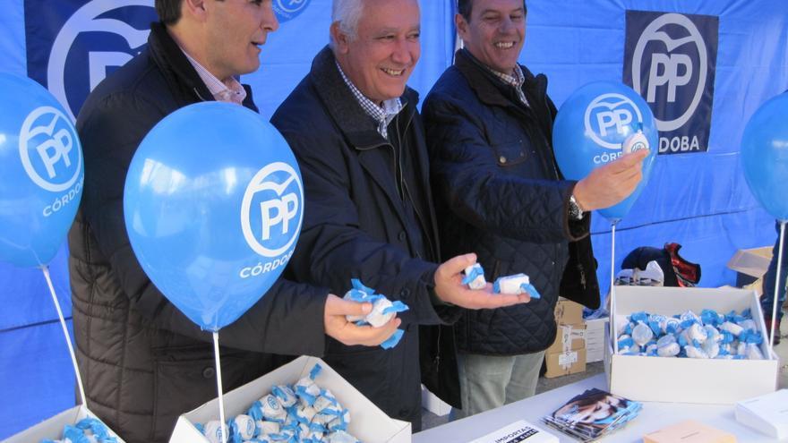 El vicesecretario general del PP, Javier Arenas, con los candidatos populares por Córdoba, reparte mantecados en su stand electoral.