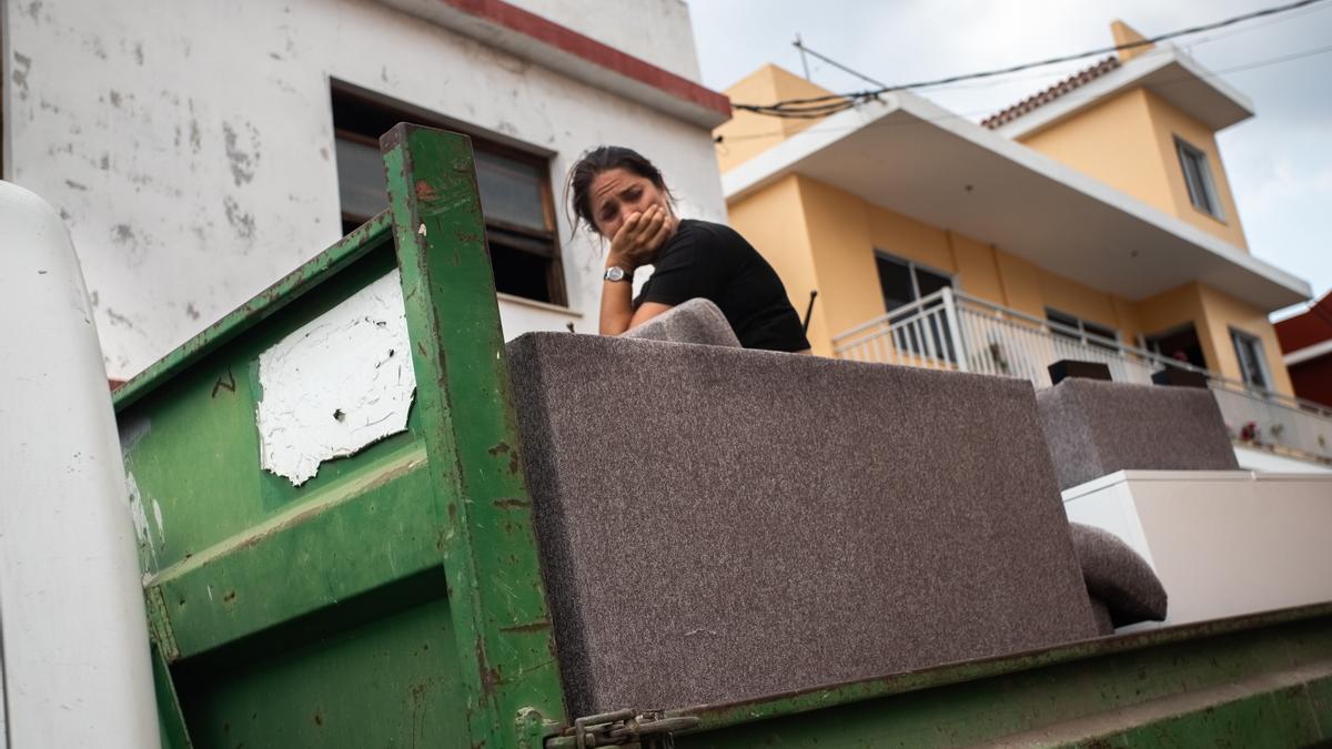 Una mujer llora sentada sobre sus cosas después de vaciar su casa por la amenaza del volcán de La Palma