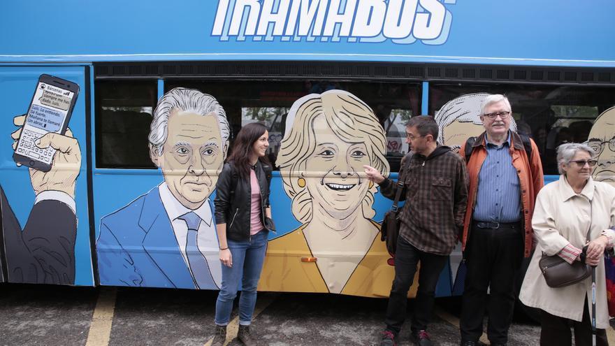 Juan Carlos Monedero, con Ione Belarra y Manolo Monereo, señala la caricatura de Aguirre en el 'tramabús' el jueves.